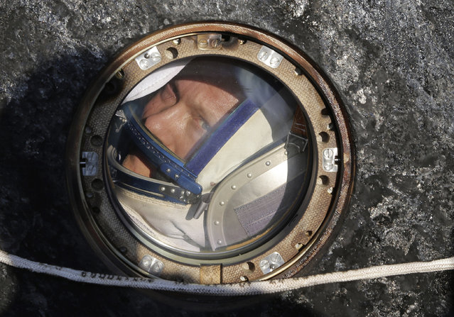 Russian cosmonaut Oleg Artemyev looks out of the Russian Soyuz TMA-12M space capsule shortly after landing southeast of Dzhezkazgan September 11, 2014. (Photo by Maxim Shipenkov/Reuters)