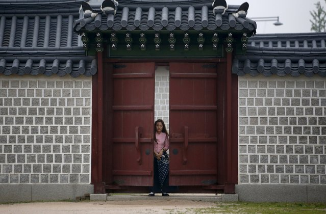 An employee in traditional costume stands behind a locked gate at Gyeongbok Palace in central Seoul, South Korea, July 13, 2015. (Photo by Kim Hong-Ji/Reuters)