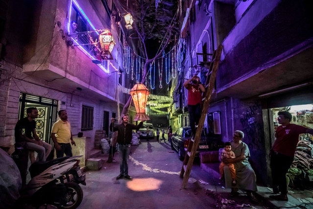 Egyptian youths decorate their residential street in preparation for the Muslim holy month of Ramadan in Cairo's Hadayek el-Maadi district, on April 21, 2020. From cancelled iftar feasts to suspended mosque prayers, Muslims across the Middle East are bracing for a bleak month of Ramadan fasting as the threat of the COVID-19 pandemic lingers. Ramadan is a period for both self-reflection and socialising. Believers fast from dawn to dusk and then gather around a family or community meal each evening of Islam's holiest month, which begins later this week and ends with Eid al-Fitr festivities (Photo by Khaled Desouki/AFP Photo)