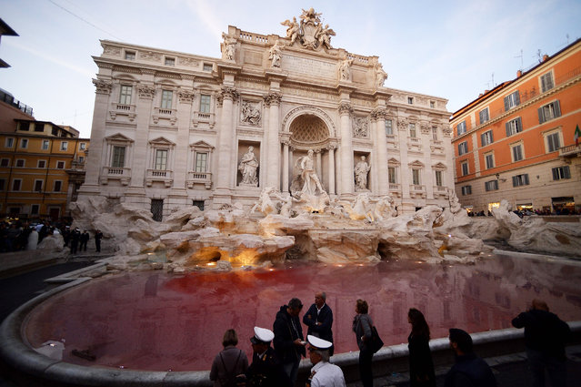 Local police stand by the Trevi fountain in Rome on October 26, 2017 after Italian activist Graziano Cecchini poured red dye into the pool, 10 years after he pulled the same stunt vandalizing one of Rome's most famous monuments. (Photo by Filippo Monteforte/AFP Photo)