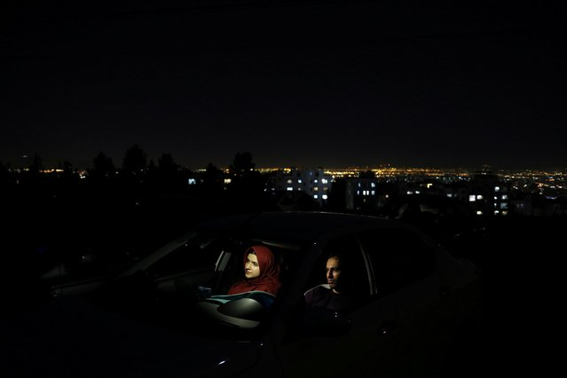 An Iranian couple sits in their car watching a movie in a drive-in cinema at the Milad Tower parking space, following the outbreak of the coronavirus disease (COVID-19), in Tehran, Iran, May 3, 2020. (Photo by Ali Khara/WANA (West Asia News Agency) via Reuters)