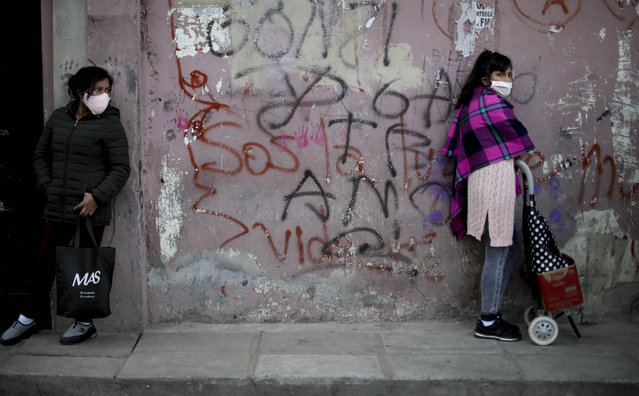 Women stand at a distance as they wait in line for a plate of food at a soup kitchen in the 1.11.14 neighborhood during a government-ordered lockdown to curb the spread of the coronavirus in Buenos Aires, Argentina, Friday, May 29, 2020. (Photo by atacha Pisarenko/AP Photo/)