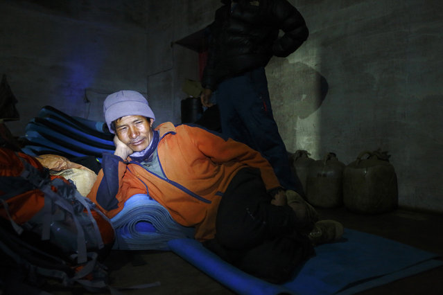 A porter rests inside a porterhouse in Tengboche, approximately 12467 feet above sea level, in Solukhumbu District May 1, 2014. (Photo by Navesh Chitrakar/Reuters)