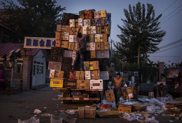 Chinese fruit vendors stack boxes on a truck at a local market on September 26, 2014 in Beijing, China. (Photo by Kevin Frayer/Getty Images)
