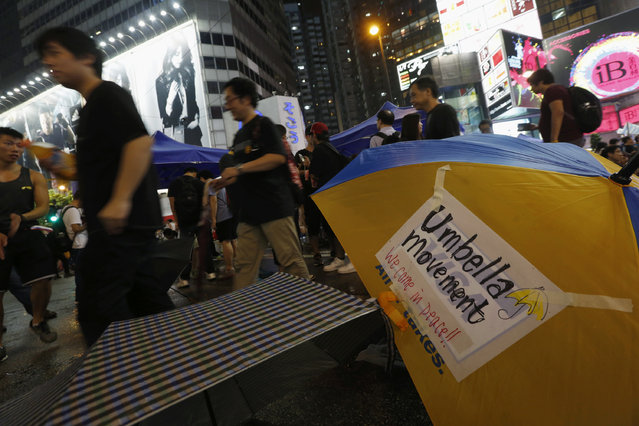 Protesters walk past an umbrella as they block the main road at Causeway Bay shopping district in Hong Kong September 30, 2014. (Photo by Bobby Yip/Reuters)