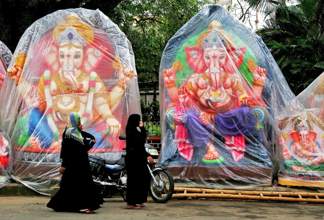 Indian Muslim women walk past idols of Hindu elephant-headed god Lord Ganesh during preparations for the upcoming Ganesh Chaturthi festival at a roadside make-shift workshop in Bangalore, India, 14 September 2014. The ten-day long Hindu festival is celebrated as the birthday of Lord Ganesh and starts on 17 September. (Photo by Jagadeesh N.V./EPA)
