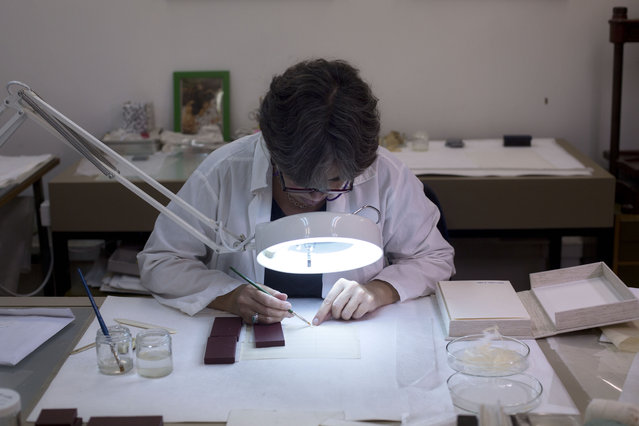 In this photo taken Sunday, October 5, 2014, a conservation expert repairs a manuscript at Israel's National Library in Jerusalem. (Photo by Sebastian Scheiner/AP Photo)