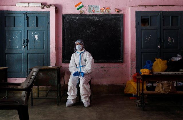 A medical worker sits inside a classroom as she takes a break at a school, which was turned into a centre to conduct tests for the coronavirus disease (COVID-19), amidst its spread in New Delhi, India on June 22, 2020. (Photo by Adnan Abidi/Reuters)