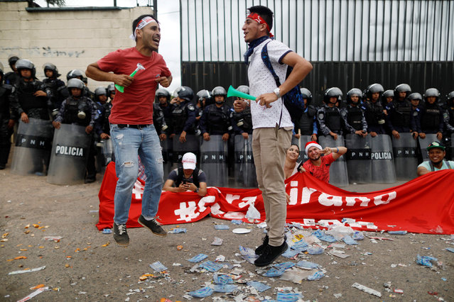 Supporters of Salvador Nasralla, presidential candidate for the Opposition Alliance Against the Dictatorship, jump in front of riot police while waiting for official presidential election results outside the warehouse of the Supreme Electoral Tribunal in Tegucigalpa, Honduras, November 29, 2017. (Photo by Edgard Garrido/Reuters)