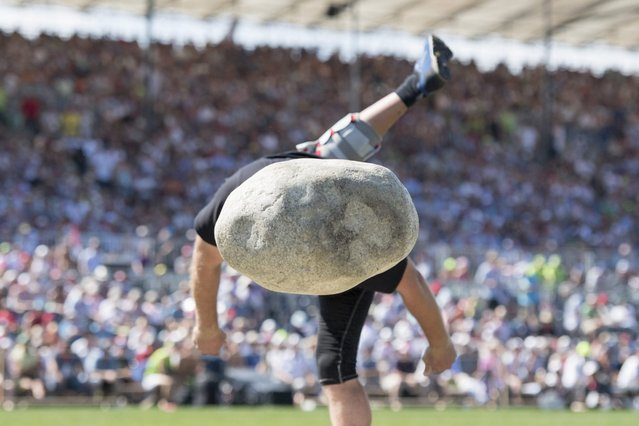 """Peter Michel competes in the stone put during the Swiss Alpine Wrestling and Herdsman Festival 2016 in Estavayer, Switzerland, 28 August 2016. The Federal Alpine Wrestling Festival takes place every three years and brings together the best alpine wrestlers to determine the """"king"""" of alpine wrestling. (Photo by Urs Flueeler/EPA)"""