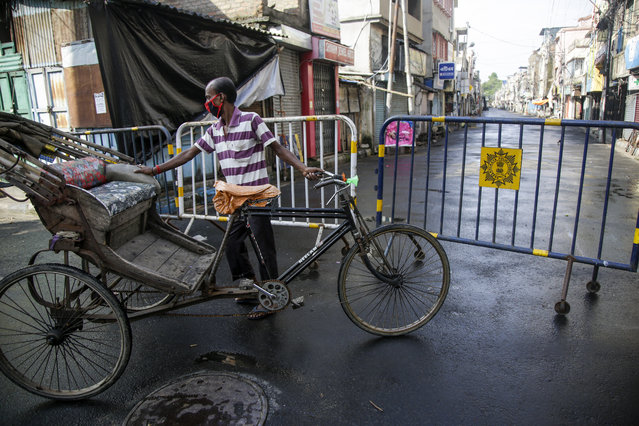 A rickshaw puller waits for passenger just outside a containment zone barricaded to prevent the spread of the coronavirus in Kolkata, India, Tuesday, July 14, 2020. (Photo by Bikas Das/AP Photo)