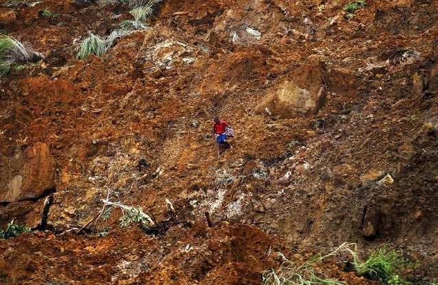 A man carrying a suitcase crosses a muddy slope at the site of a landslide at the Koslanda tea plantation near Haldummulla, October 30, 2014. (Photo by Dinuka Liyanawatte/Reuters)