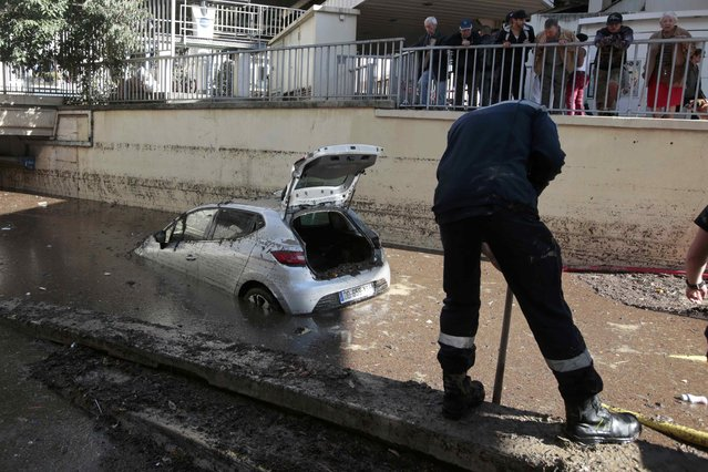 People watch as a French fireman works near an abandoned car after flooding caused by torrential rain in Cannes, France, October 4, 2015. (Photo by Eric Gaillard/Reuters)