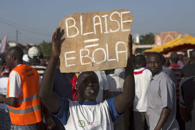 A protester holds a sign, which refers to President Blaise Compaore, during a demonstration in Ouagadougou, Burkina Faso October 28, 2014. (Photo by Joe Penney/Reuters)