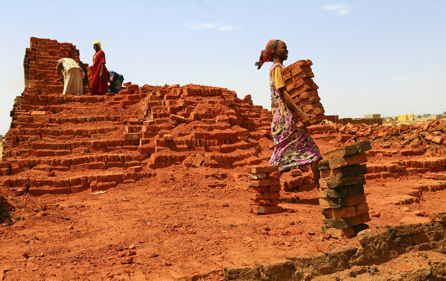 A woman carries mudbricks in Abu Shock IDPs camp in Al Fashir, capital of North Darfur, Sudan, September 6, 2016. (Photo by Mohamed Nureldin Abdallah/Reuters)