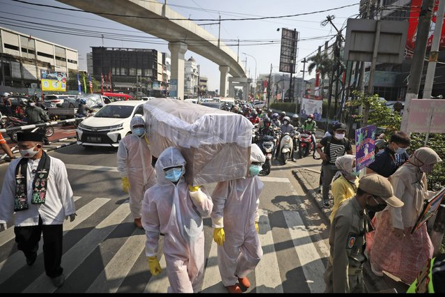 Government officials in protective suits carry a mock coffin as they walk around a busy intersection during a coronavirus awareness campaign to remind people of the risk of contracting COVID-19 and to always obey health protocols to curb the spread of the outbreak in Jakarta, Indonesia, Friday, August 28, 2020. (Photo by Dita Alangkara/AP Photo)