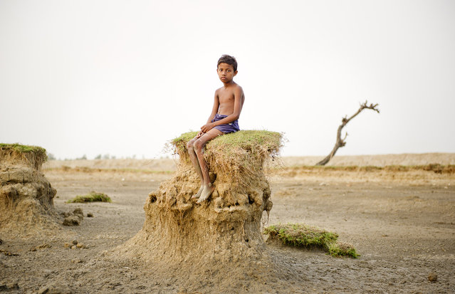 """""""Ghoramara island is located on a delta region in West Bengal. Due to the dramatic increase in sea level, resulting from the effects global warming since the 1960s, the shores of this island are being perpetually washed away. Since the 1980s more than 50% of the territory has vanished due to erosion by the sea. Many of the people still living on the island are farmers and fishermen who depend on the island's resources for their livelihoods. According to a civil servant I met, in 20-25 years the Indian government could abolish the island and has already formulated a plan to evacuate villagers to another island named Sagar. However, this evacuation plan does not ensure any financial support or compensation for those having to relocate their lives. I situated villagers on the shore and took portraits of them in juxtaposition with the beauty of the vanishing island. There will come a day when these people will have no choice but to move out of their homeland"""". (Photo and comment by Daesung Lee, Korea/2013 Sony World Photography Awards"""