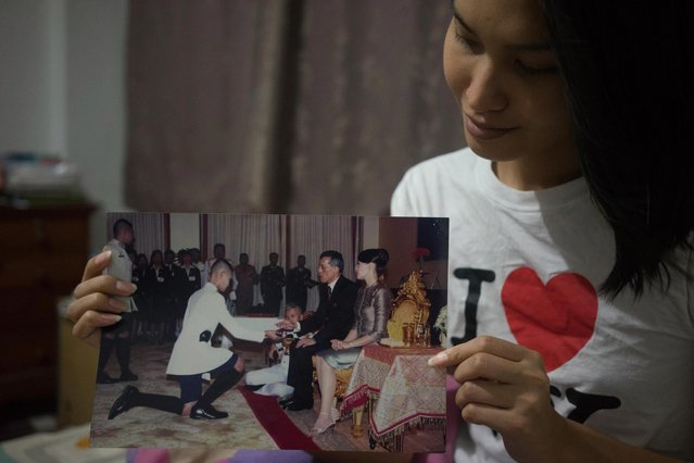 "Kritchaya ""Lolita"" Boonhor shows a photo of her graduation ceremony from King's College in Nakhon Pathom, in her bedroom in Bangkok, Thailand, 02 December 2017. She is the one kneeling (C-L) in front the then Thai Crown Prince Maha Vajiralongkorn (C-R). (Photo by Lola Levan/EPA/EFE)"