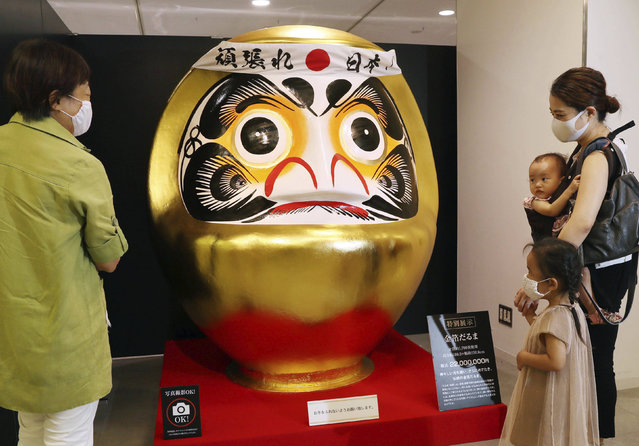 A golden Daruma statue is displayed during an event at Osaka Takashimaya department store in Osaka City, Osaka Prefecture on August 13, 2020. 1.8-meter-high Daruma which demands the end of Coronavirus pandemic is made of about 1,700 gold leaves and costs JPY22,000,000 (about US$205,000) including tax. (Photo by The Yomiuri Shimbun via AP Images)