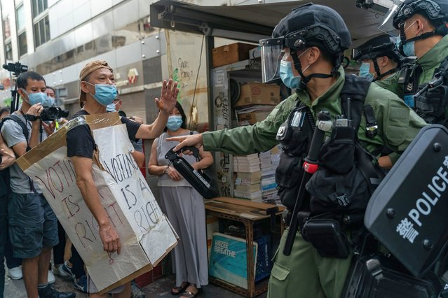 A man wearing a Voting Is A Right costome stand off with riot police during an anti-government protest on September 6, 2020 in Hong Kong, China. Nearly 300 people were arrested during the protest against the government's decision to postpone the legislative council election due to the Covid-19 and the newly imposed national security law. (Photo by Anthony Kwan/Getty Images)