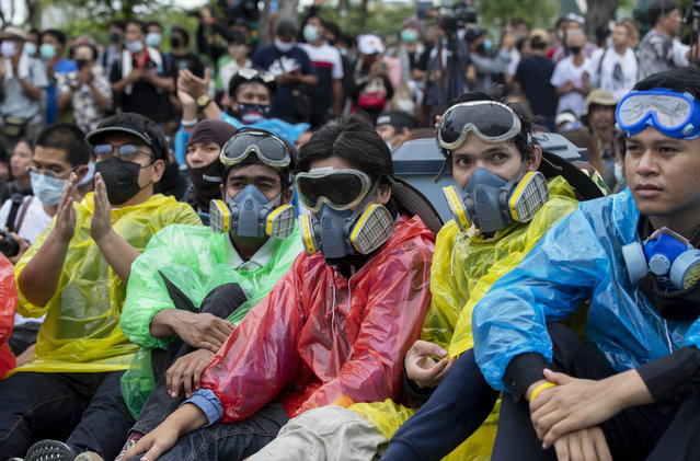 Pro-democracy protesters wearing protective masks sometimes used to avoid tear gas sit on the road during a march near Sanam Luang in Bangkok, Thailand, Sunday, Septemner 20, 2020. The mass student-led rally that began Saturday is the largest in a series of protests this year, with thousands camping overnight near the royal palace, demanding for new elections and reform of the monarchy. (Photo by Gemunu Amarasinghe/AP Photo)