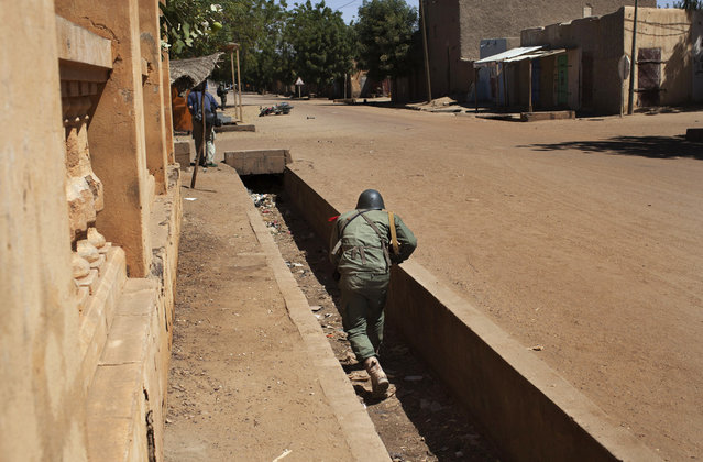 A Malian soldier runs in an empty gutter during fighting with Islamists in Gao, on February 21, 2013. (Photo by Joe Penney/Reuters/The Atlantic)