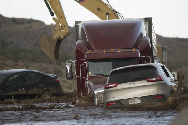 Workers dig out cars and trucks mired in mud and debris on State Route 58 near Tehachapi, California, about 60 miles (97km) outside of Los Angeles, October 17, 2015.  A mudslide on Thursday left nearly 200 vehicles, including 75 semi-trailer trucks, stuck in up to five feet of mud, local sheriff's spokesman Ray Pruitt said. (Photo by David McNew/Reuters)