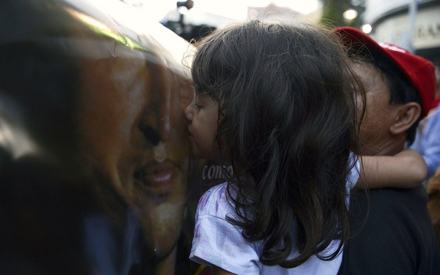 In Caracas, girl kissing photo of Hugo Chavez after the death of the President of Venezuela. (Photo by Juan Barreto/AFP Photo)