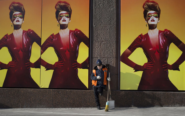 An Asian municipal worker  plays on his cell phone as he rests at an advertising  in Moscow,  Russia, Tuesday, March 12, 2013. (Photo by Alexander Zemlianichenko/AP Photo)