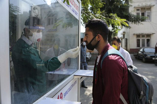 A health worker collects a nasal swab sample to test for COVID-19 at a government hospital in Jammu, India, Saturday, October 17, 2020. The Health Ministry on Saturday reported 62,212 new cases in the past 24 hours, raising India's total to more than 7.4 million, second in the world behind the U.S. (Photo by Channi Anand/AP Photo)