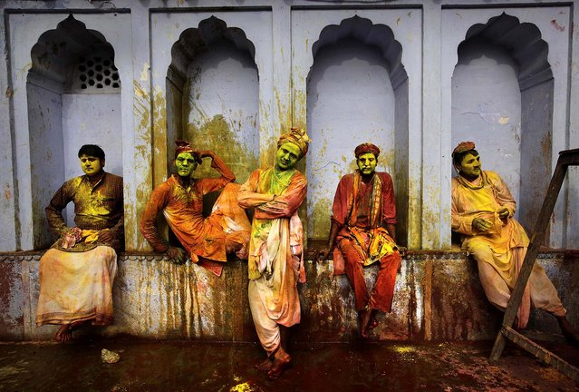 Villagers from Nandgaon wait for the arrival of villagers from Barsana to play Lathmar Holi at the Nandagram temple famous for Lord Krishna and his brother Balram, in Nandgaon, India, on Friday, on March 22, 2013. (Photo by Manish Swarup/Associated Press)