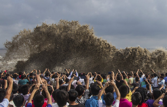 Visitors take pictures of tidal waves under the influence of Typhoon Usagi in Hangzhou, Zhejiang province, September 22, 2013. (Photo by Chance Chan/Reuters)