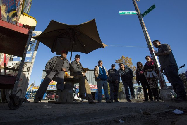 Workers gather to play a coin toss game on a street corner in the Willets Point area of Queens in New York October 30, 2015. (Photo by Andrew Kelly/Reuters)