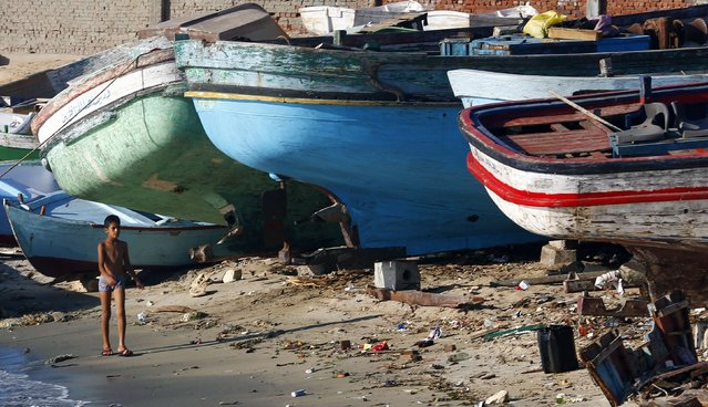 """A boy walks past boats docked at the entrance gate of the fishermen's village in the El Max area of the Mediterranean city of Alexandria September 12, 2014.  El Max, where hundreds of boats dart through the canals, has been called the """"Venice of Egypt"""" for its waterways and relaxed atmosphere. Its fishermen, however, worry about how they will make ends meet on meagre earnings they  say are being reduced further by polluted waters that are making fishing more difficult. (Photo by Amr Abdallah Dalsh/Reuters)"""