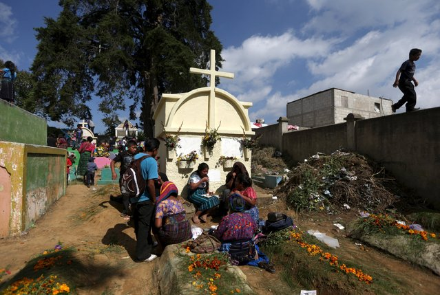 People eat next to a grave during an All Saints celebration with kites in the cemetery of Santiago Sacatepequez, Guatemala, November 1, 2015. Dating back 116 years, the tradition of flying kites in the cemetery  of of Santiago Sacatepequez, integrates the Catholic feast of All Saints with ancient Mayan practices of honouring the dead. It is believed that the kites connect the living and the dead during the all saints day celebration. (Photo by Jorge Dan Lopez/Reuters)