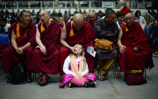A girl sits by buddhist monks during a public meeting of the Tibetan spiitual leader, the Dalai Lama, after he was awarded the award of Minorities by province of Bolzano on April 11, 2013 in Trento. (Photo by Olivier Morin/AFP Photo)
