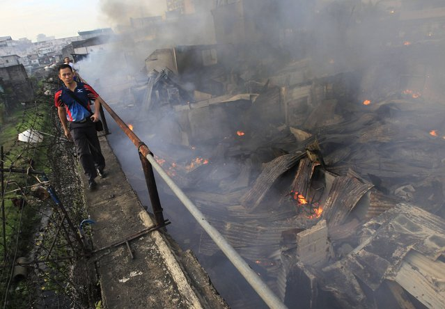 A man walks past burning houses after a fire broke out at a slum area in Manila December 11, 2014. Around 200 houses were gutted by the fire in the early morning of Thursday, which left an estimated 500 families homeless and one firefighter injured, local media reported. (Photo by Romeo Ranoco/Reuters)