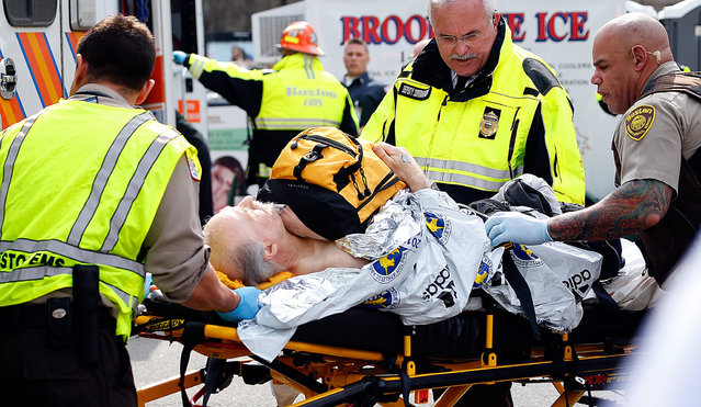 A man is loaded into an ambulance after he was injured by one of two bombs exploded during the 117th Boston Marathon near Copley Square on April 15, 2013 in Boston, Massachusetts. (Photo by Jim Rogash)