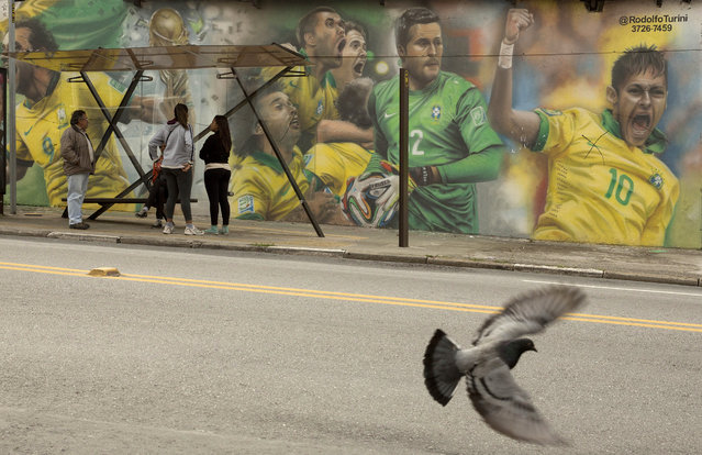 In this May 26, 2014 file photo, a mural of Brazilian soccer player Neymar, right, and others cover a wall by a bus stop in Sao Paulo, Brazil. The mural was painted by Brazilian street artist Rodolfo Turini ahead of the World Cup soccer tournament. (Photo by Andre Penner/AP Photo)