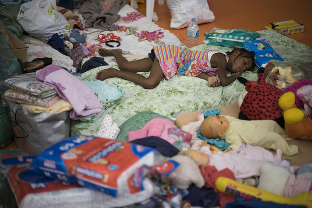 A girl rests on a mattresses in a sports arena after residents were displaced by dams that burst in Mariana, Minas Gerais state, Brazil, Friday, November 6, 2015. (Photo by Felipe Dana/AP Photo)