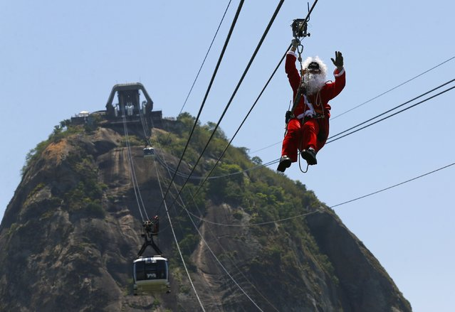 A man dressed as Santa Claus hangs on a cable for cable cars while descending from the Sugar Loaf Mountain in Rio de Janeiro December 18, 2014. (Photo by Ricardo Moraes/Reuters)