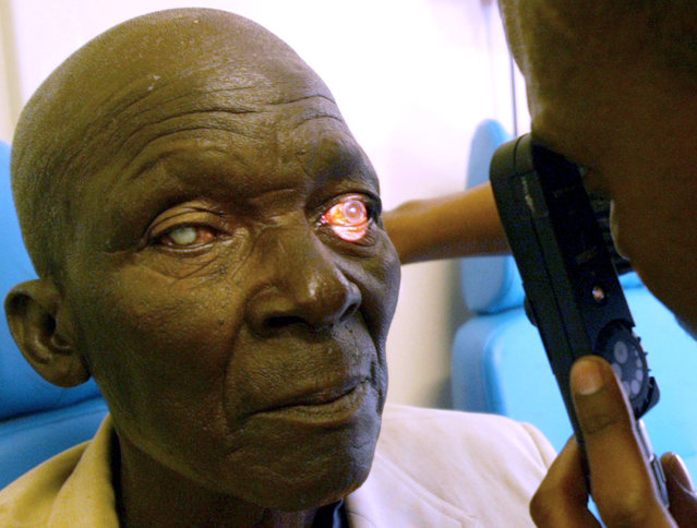 A student doctor conducts an eye test at Kimberley train station in South Africa June 29, 2004. (Photo by Juda Ngwenya/Reuters)