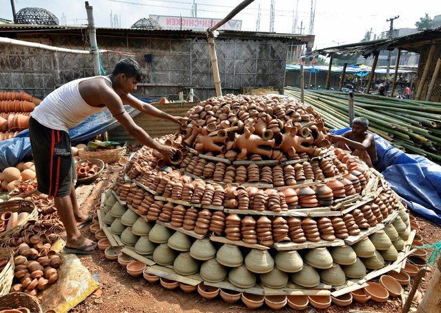 Potters harden earthen lamps, which are used to decorate temples and homes during the Hindu festival of Diwali, on a hearth at a workshop in Guwahati, India, October 22, 2016. (Photo by Anuwar Hazarika/Reuters)