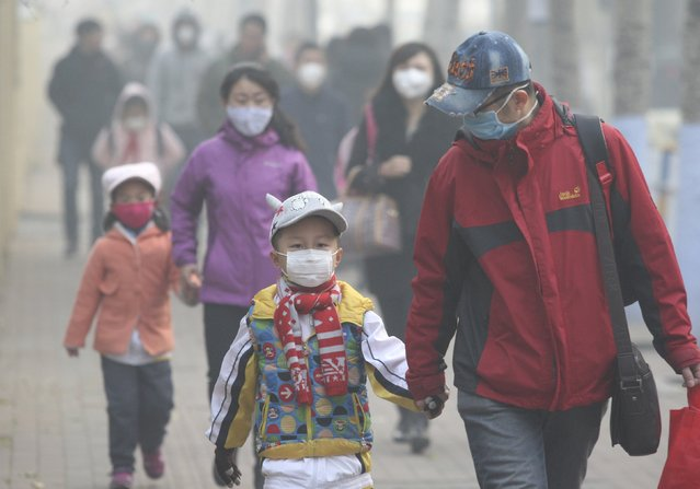 Young students and their parents wearing masks walk along a street on a hazy day in Harbin, Heilongjiang province, China, November 3, 2015. Some kindergartens and schools were closed as severe air pollution hit northeastern Chinese city of Harbin on Tuesday, local media reported. (Photo by Reuters/Stringer)
