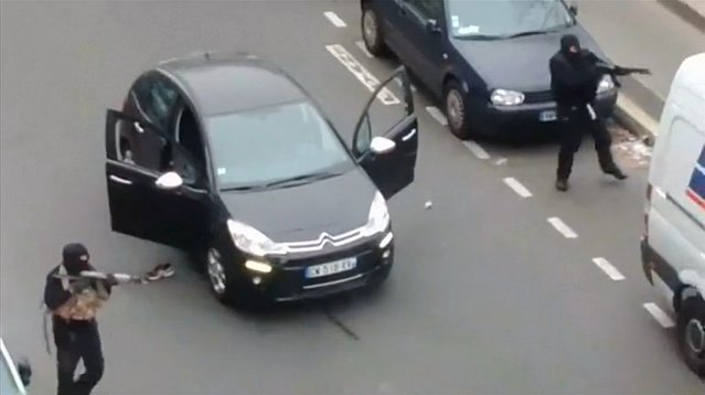 Gunmen flee the offices of French satirical newspaper Charlie Hebdo in Paris, in this still image taken from amateur video shot on January 7, 2015, and obtained by Reuters. (Photo by Reuters/Handout via Reuters TV)