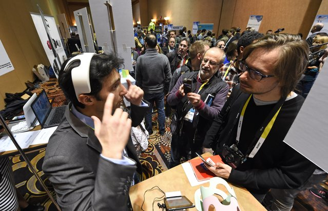 Yohan Attal of myBrain Technologies wears the Melomind headset at CES Unveiled, the opening event for the media preview days at the 2015 Consumer Electronics Show, January 4, 2015 in Las Vegas, Nevada. A fifteen minute session wearing the connected headset helps to control stress and provides feedback for training in stress reduction.  The device can be pre-ordered online for USD $299. (Photo by Robyn Beck/AFP Photo)
