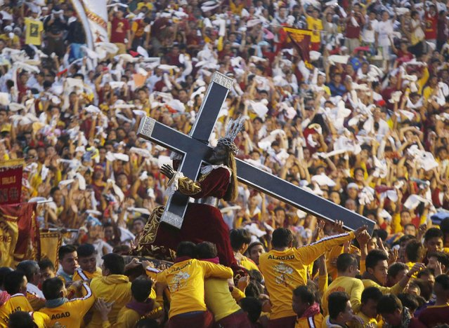 Devotees carry the Black Nazarene at the start of an annual procession in Manila, January 9, 2015. (Photo by Erik De Castro/Reuters)