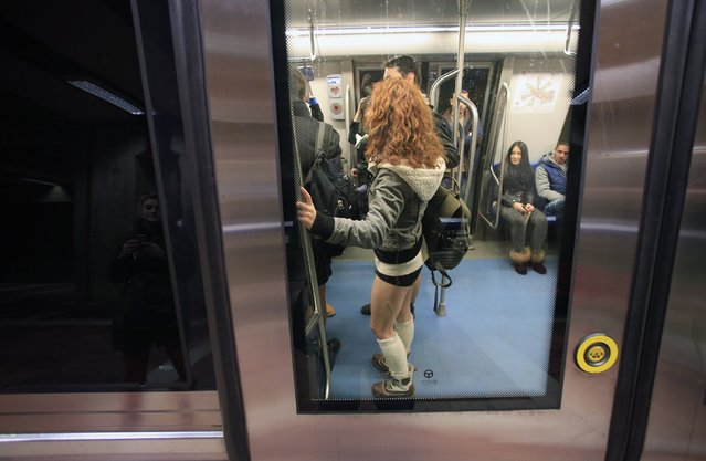 """A passenger without pants stands inside a subway train during """"The No Pants Subway Ride"""" in Bucharest January 11, 2015. (Photo by Radu Sigheti/Reuters)"""