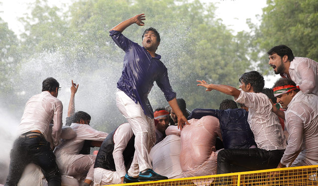 Indian security personnel use water canon to disperse the Youth Congress activists as they try to cross the police barricade during a protest in New Delhi, India, 30 November 2015. Hundreds of Youth Congress activists and supporters protested to condemn the rising intolerance and recent communal violence in India. (Photo by Harish Tyagi/EPA)