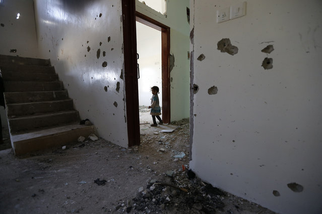 A girl is seen in her family's flat damaged during a police raid on a nearby hideout of al Qaeda militants in the Arhab region north of the Yemeni capital Sanaa May 27, 2014. (Photo by Khaled Abdullah/Reuters)